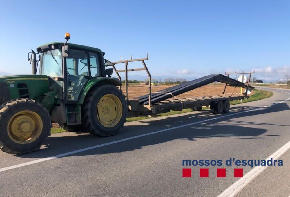 Les bigues de ferro sobresortien el remolc del tractor