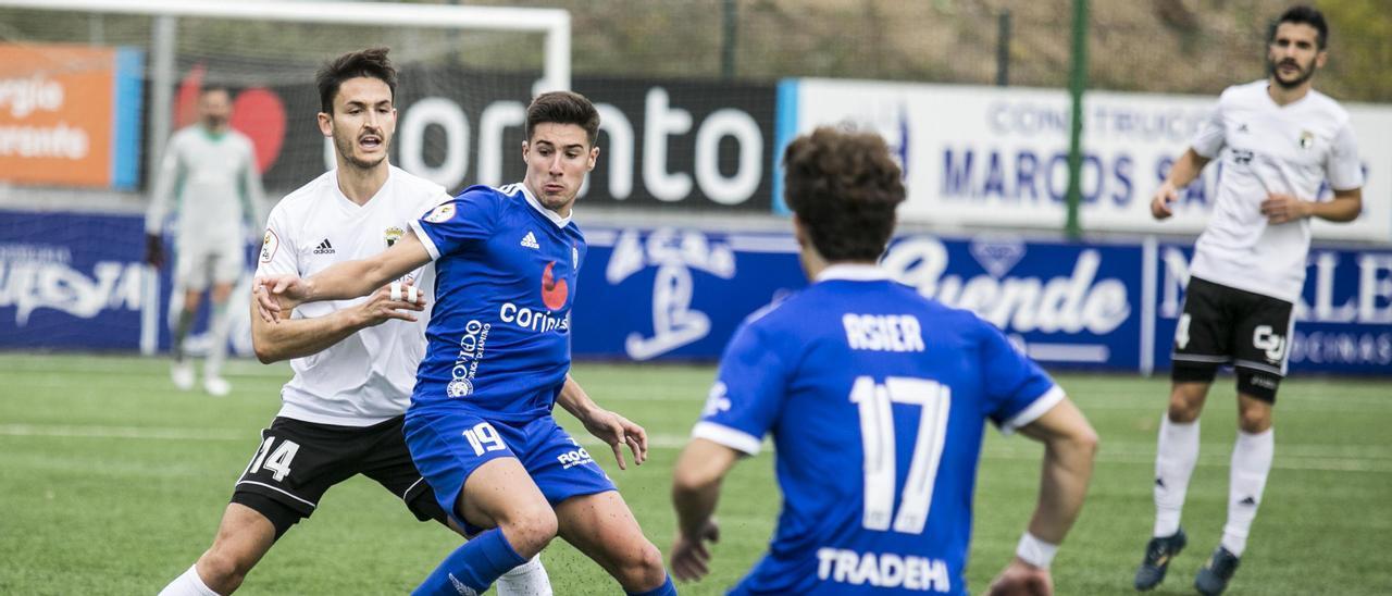 Javi Martón, disputa el balón a un jugador del Burgos
