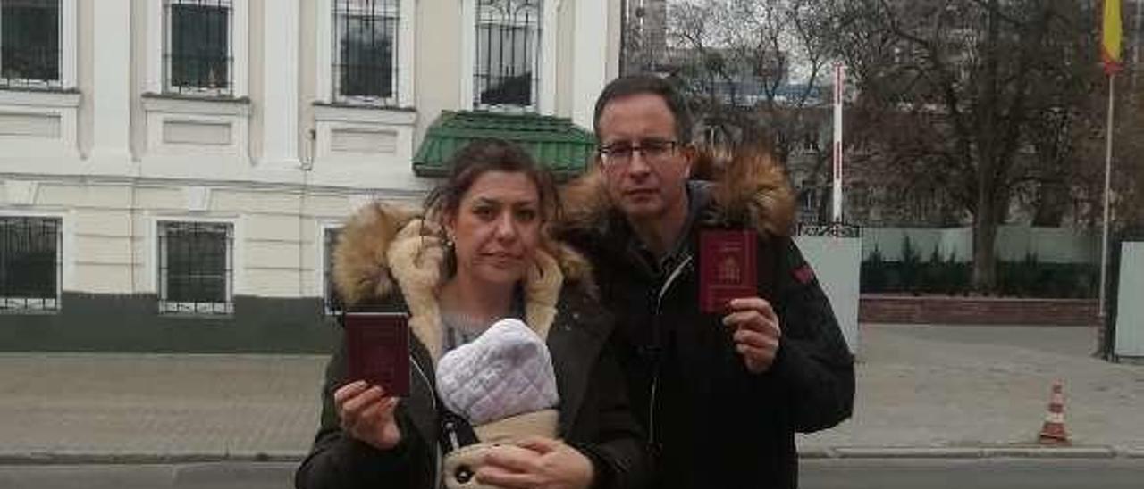 Silvia Fernández, con su bebé en brazos, y Javier Palencia, ante el consulado español en Kiev, con sus pasaportes en la mano.