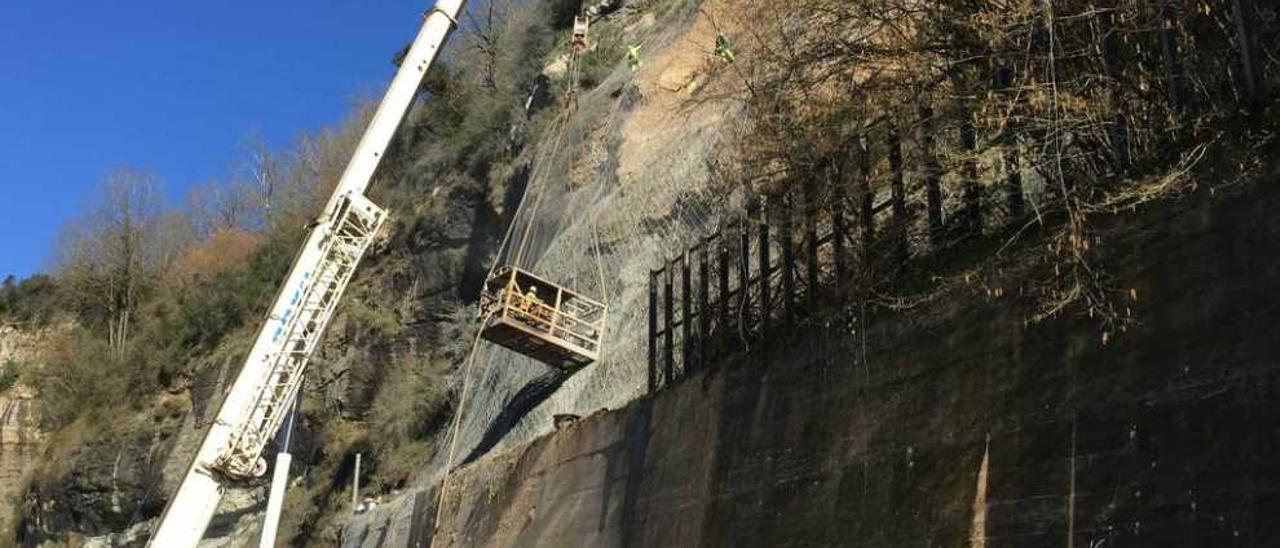 Operarios perforan la ladera del argayón para introducir bulones, ayer.