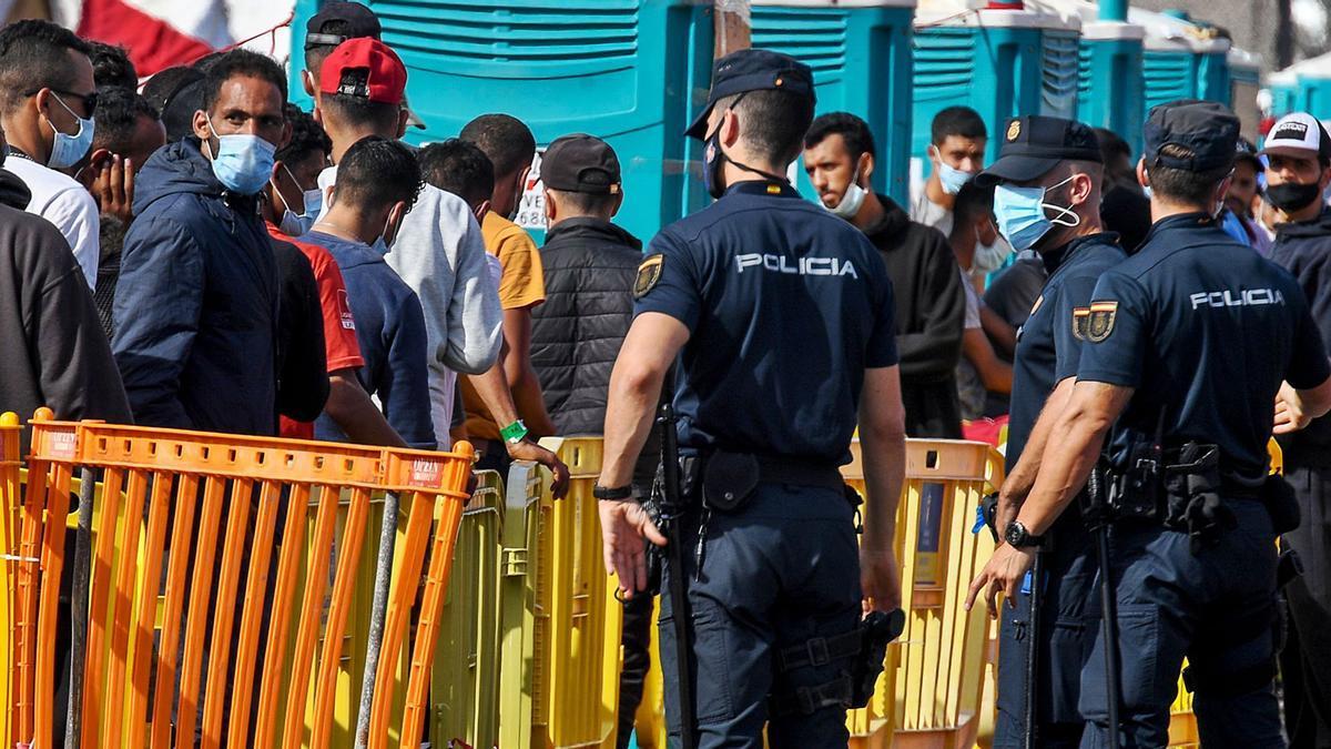 Agentes de policía en el control de los migrantes que llegaron en noviembre a puerto de Arguineguín, entonces atestado. | | JUAN CARLOS CASTRO
