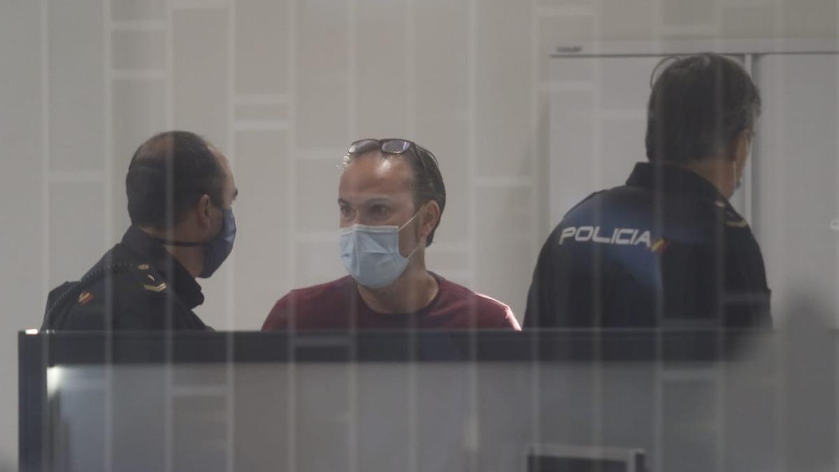 El concejal de Podemos Juan Alcántara, en el juzgado, flanqueado por dos policías.