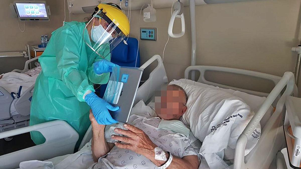 Un sanitario ayuda a realizar una videollamada a un paciente.     // L.O.