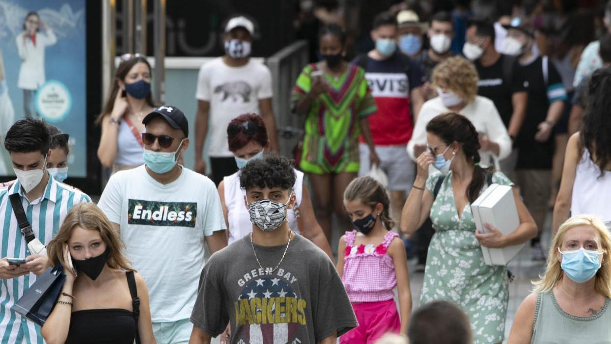 Varias personas pasean por el centro de València con mascarilla.