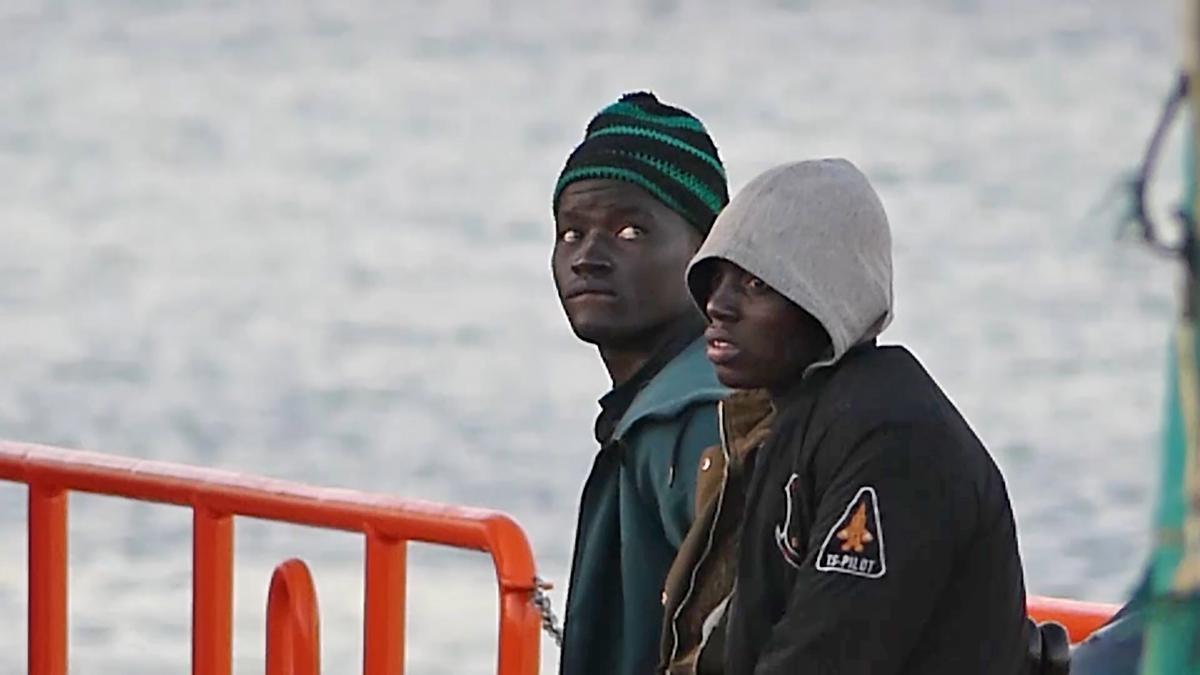 Dos migrantes llegan al puerto de Arguineguín.