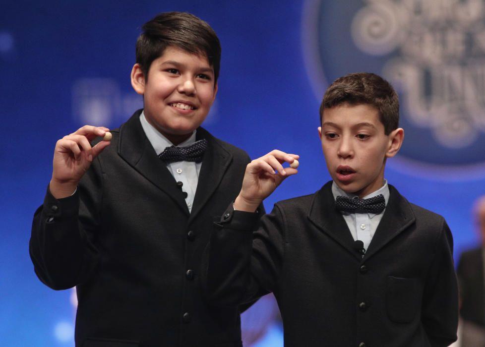 Los niños de San Ildefonso Ilyas Arouh (d) y Samuel Dávalos muestran las bolas del 81.610, octavo y último premio del Sorteo de la Lotería de Navidad.