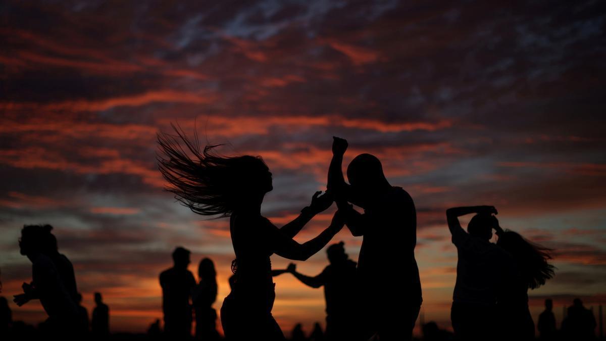 La gente baila para celebrar la víspera del solsticio de verano durante la puesta de sol en Copenhague.
