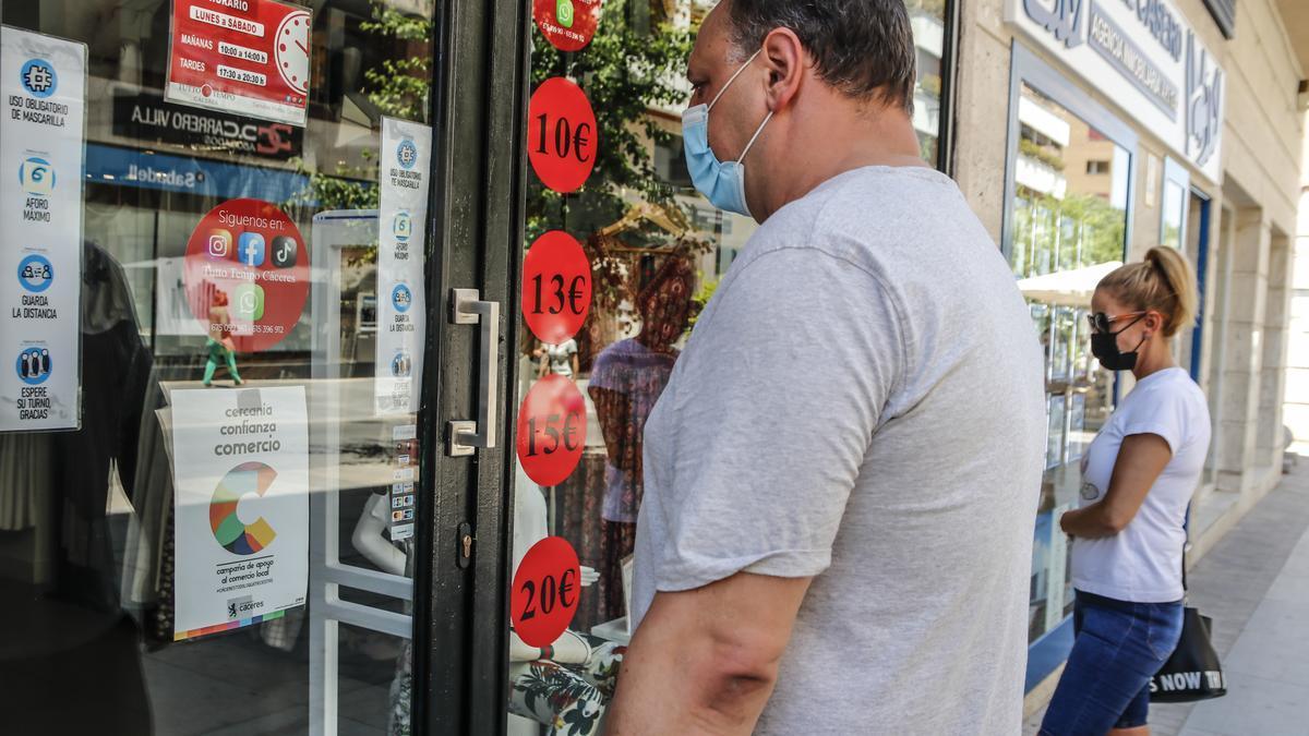 Escaparate y puerta de un establecimiento de la calle San Pedro de Alcántara con el cartel de la campaña Comercio con C de Cáceres.