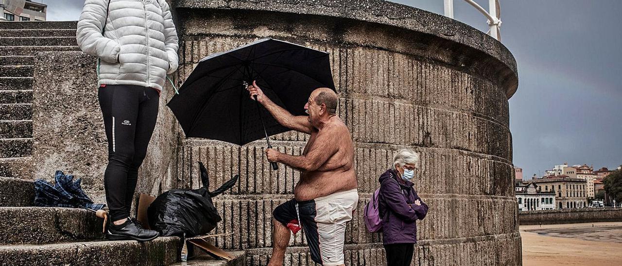 Un hombre abre un paraguas en La Escalerona tras bañarse en la playa de San Lorenzo. | MANU BRABO