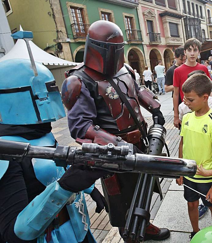 """Dos personajes de """"Star Wars"""" enseñan su armamento a unos niños   R. S. / M. V."""