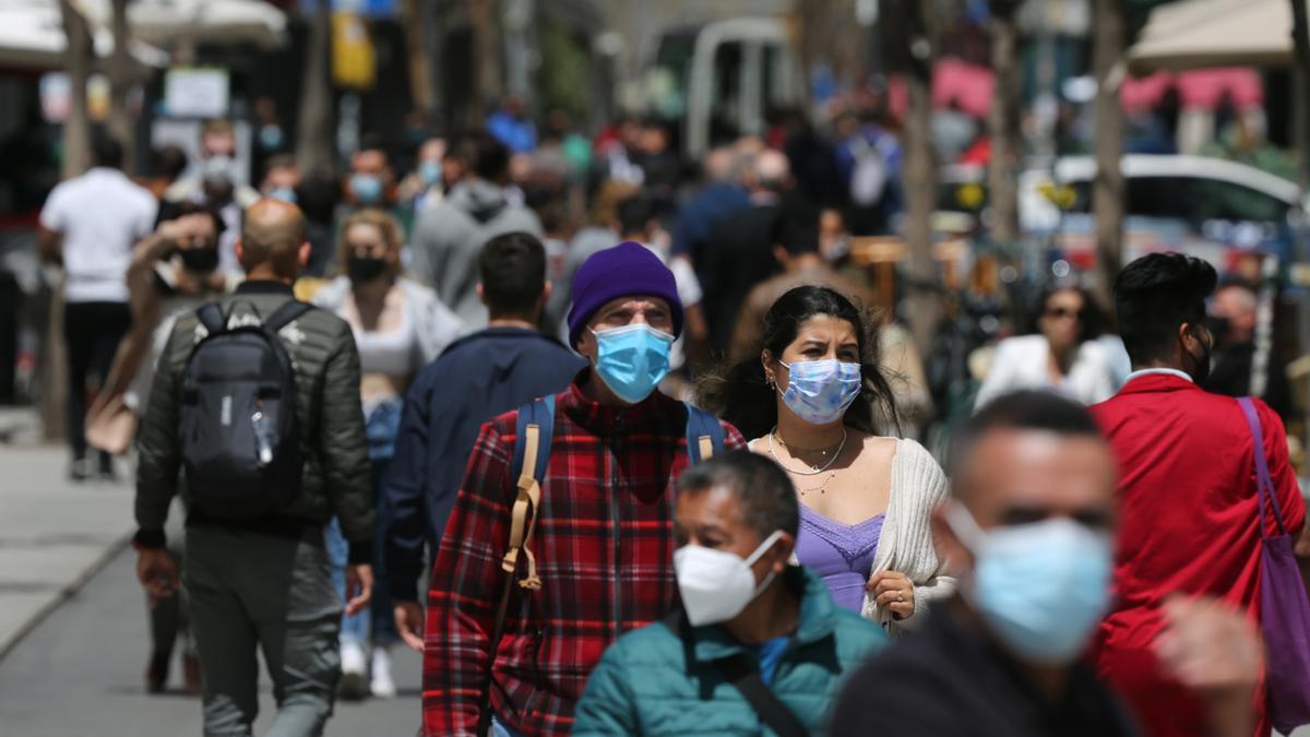 Varias personas con mascarilla caminan en una calle de Madrid.