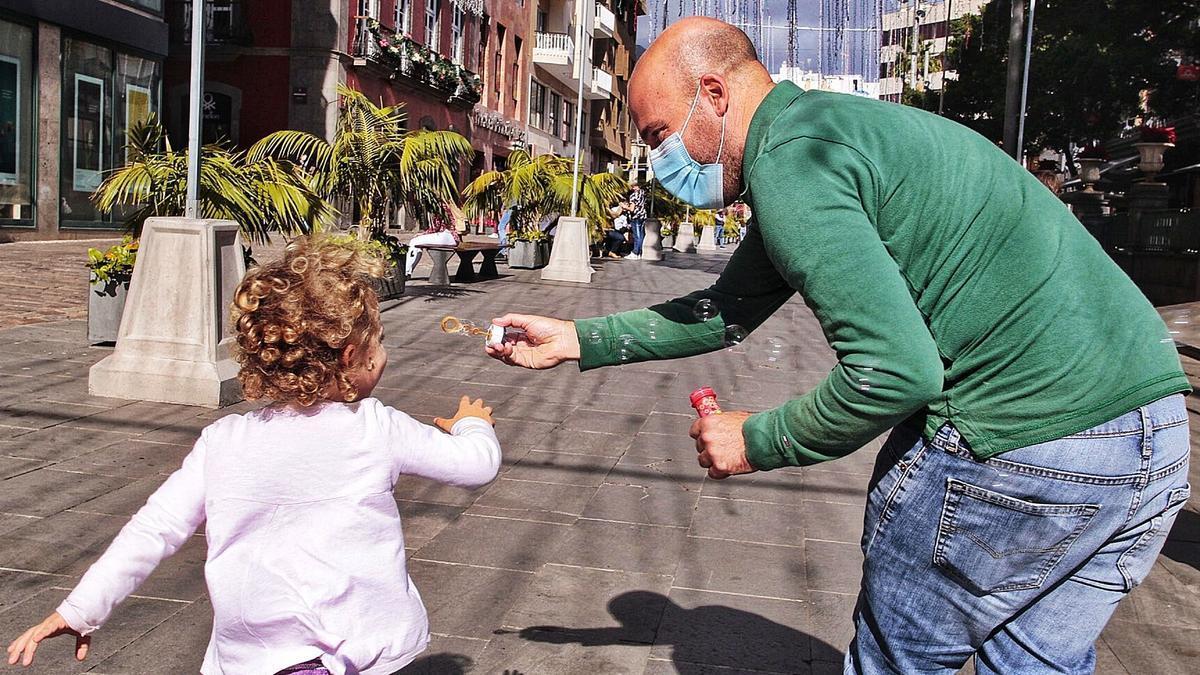 Un padre juega con su hija en las inmediaciones de la plaza del Príncipe en Santa Cruz de Tenerife.