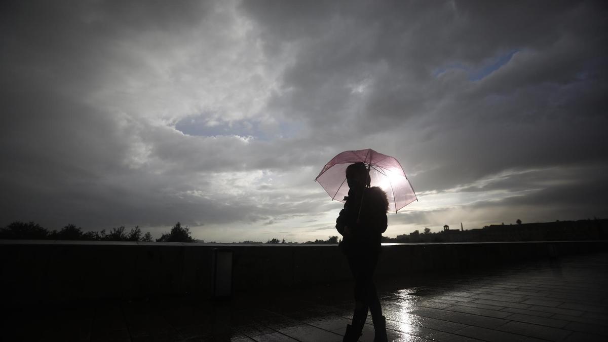 Una mujer camina con paraguas