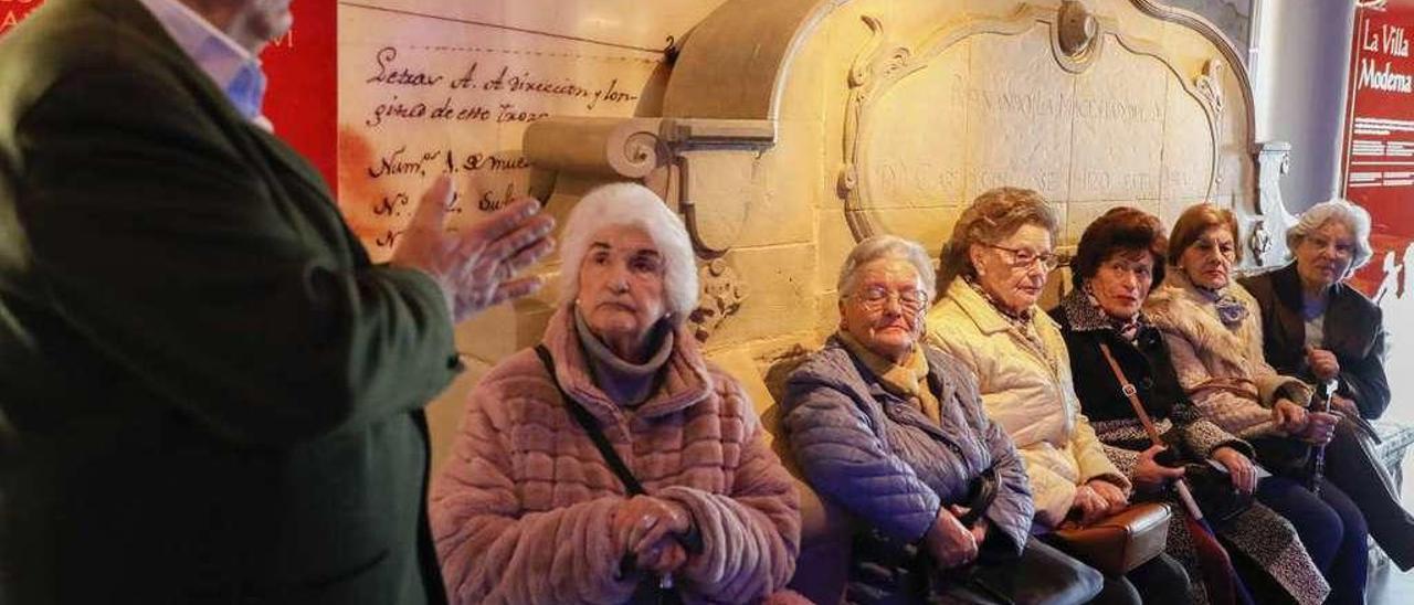 El grupo de usuarios de teleasistencia atiende a las explicaciones en el Museo de la Historia Urbana.
