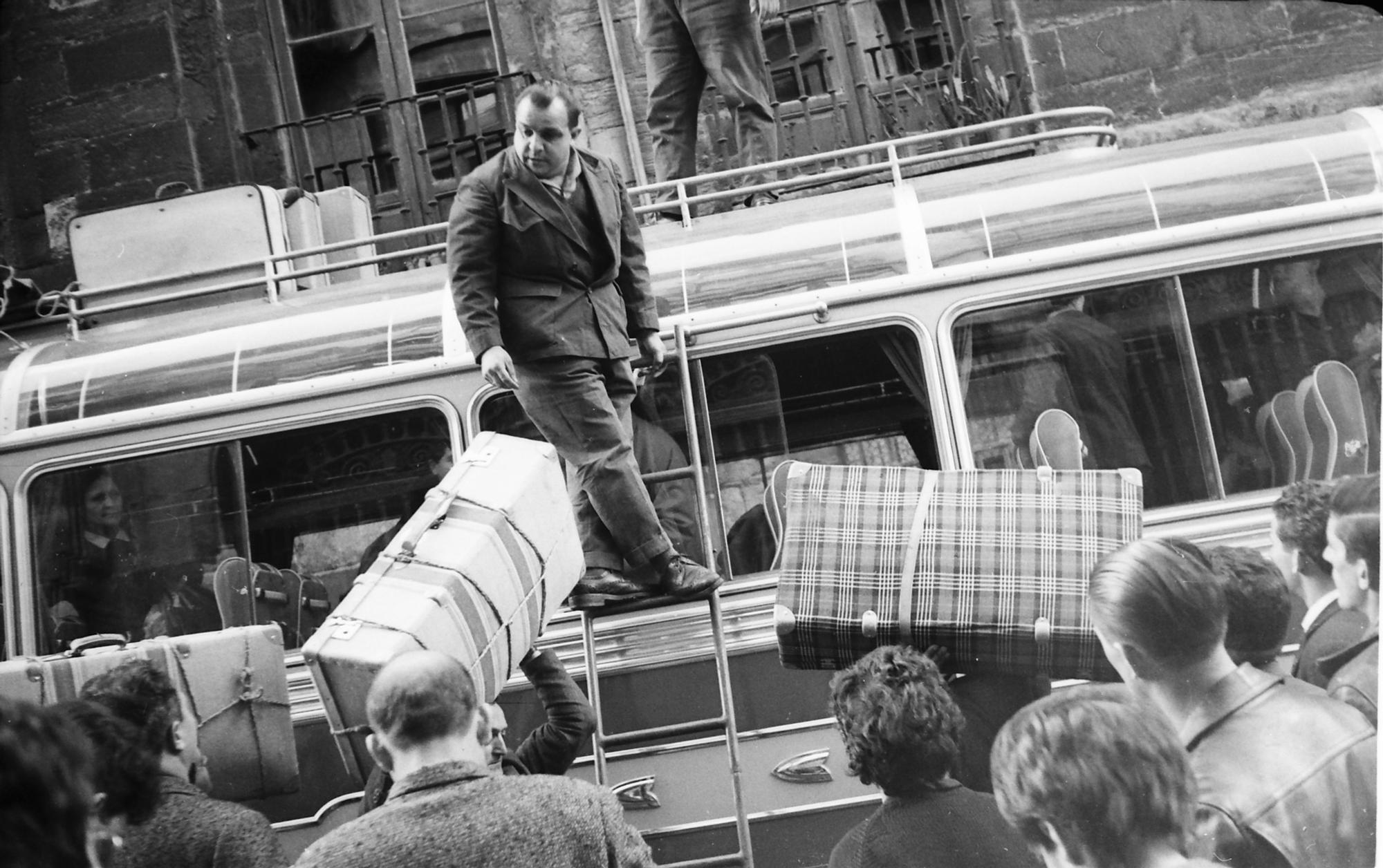 Subiendo bultos al maletero de un autocar. h. 1970.