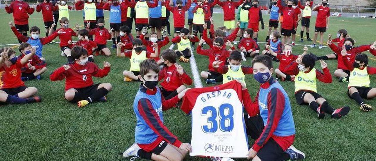 En primer término, por izquierda, Pablo Jiménez-Alfaro Álvarez y Fernando Casado Criado sujetan la camiseta firmada de Gaspar como regalo para el club en el que se formó, junto a varios de los componentes de la cantera de La Asunción, ayer, en la Laboral.