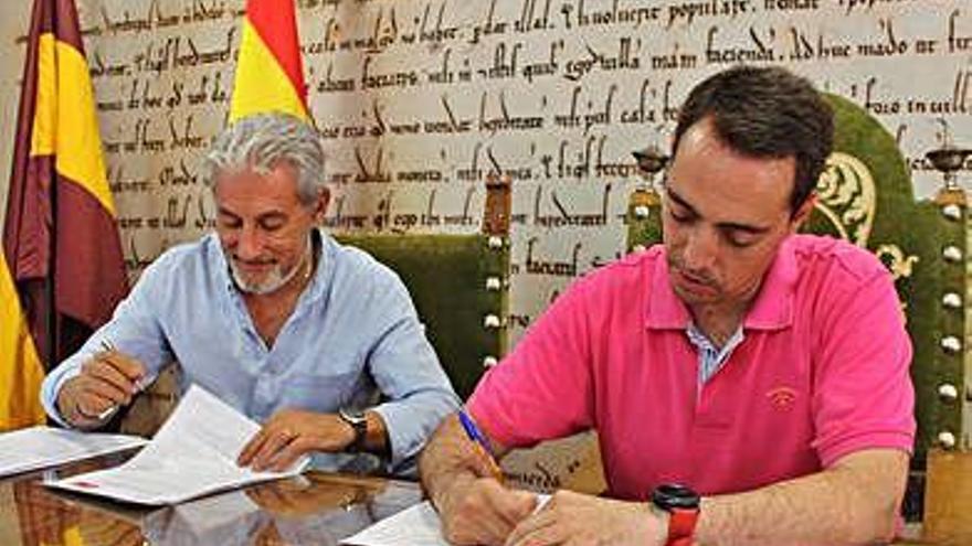 De izquierda a derecha, Manuel Burón (IU) y Luciano Huerga (PSOE) firmando el acuerdo de Gobierno.