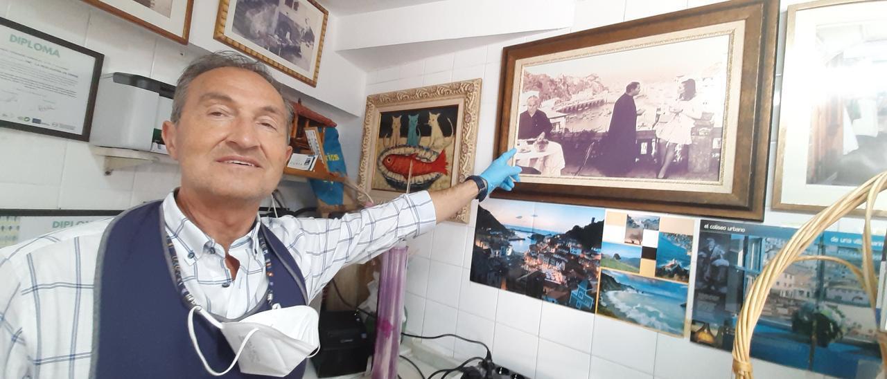 Manuel Fernández, en su pescadería, señalando el fotograma de la participación de su abuela en la cinta.