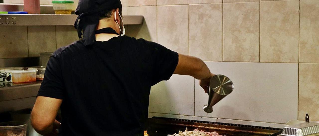 Hernán, cocinero del restaurante Jalisco, prepara carne parar burritos. | MARTA NEVOT