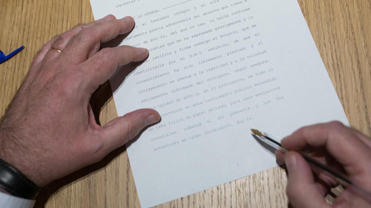 Una persona firma la escritura de un testamento ante notario.
