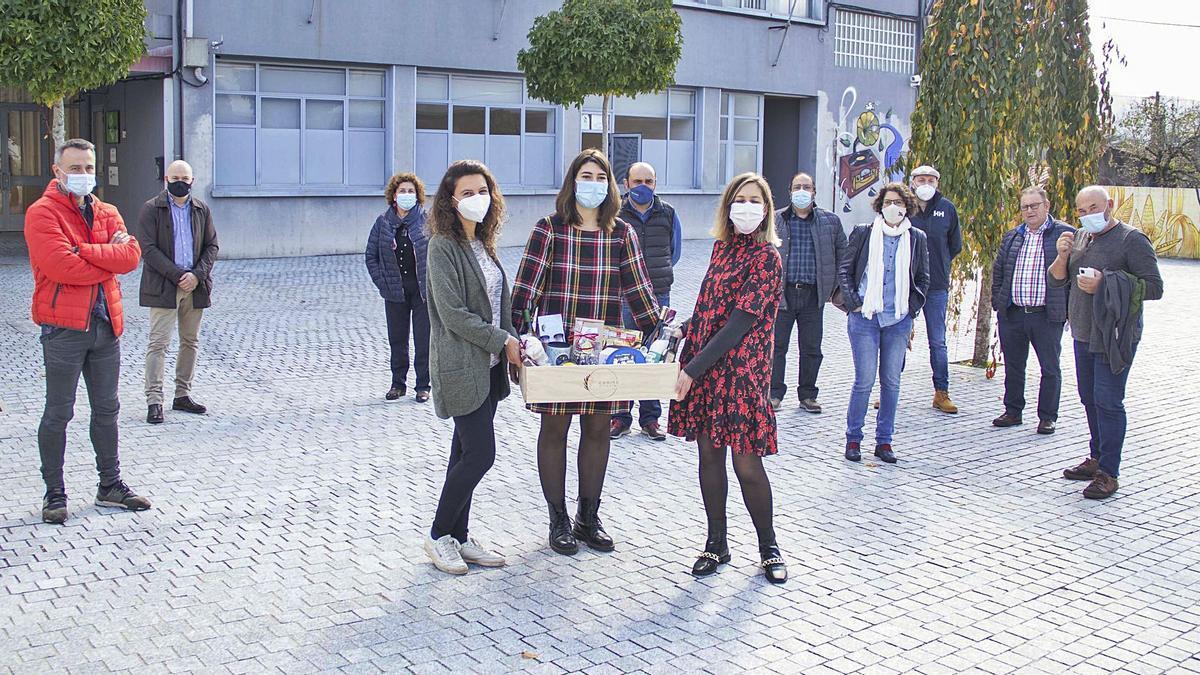 Las tres integrantes de la cooperativa posan con la cesta de Navidad rodeadas de varios de los productores. |  // BERNABÉ/ANA AGRA