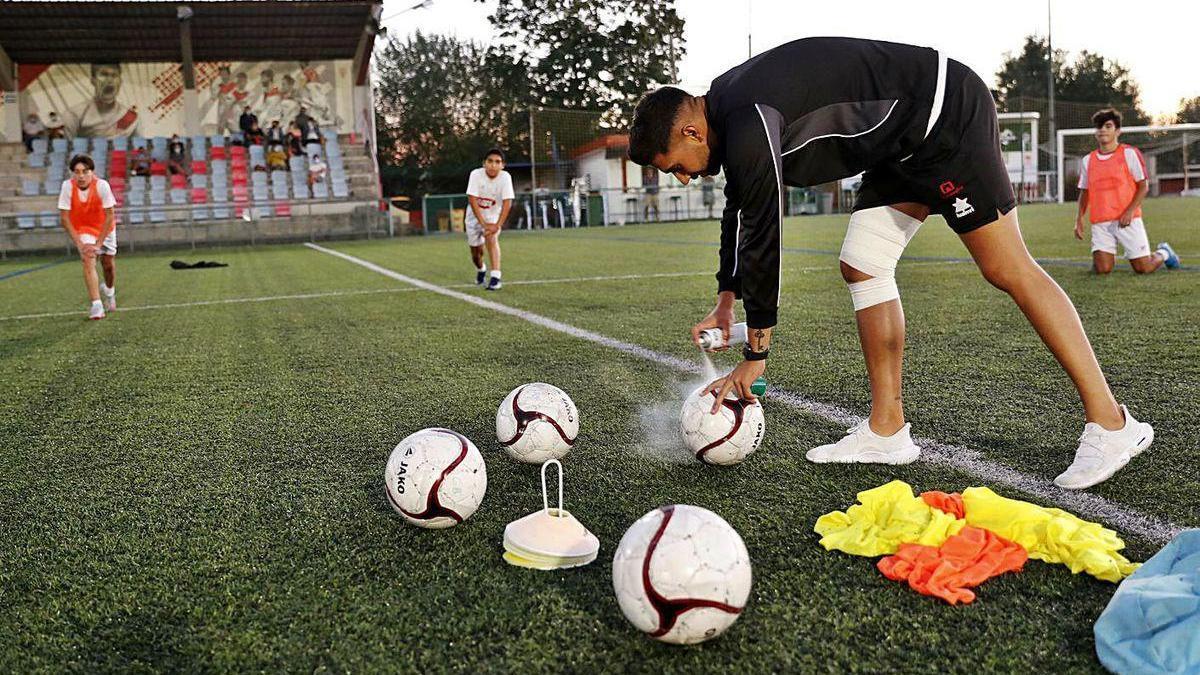 Un técnico desinfecta los balones durante un entrenamiento de un equipo juvenil del Val Miñor.