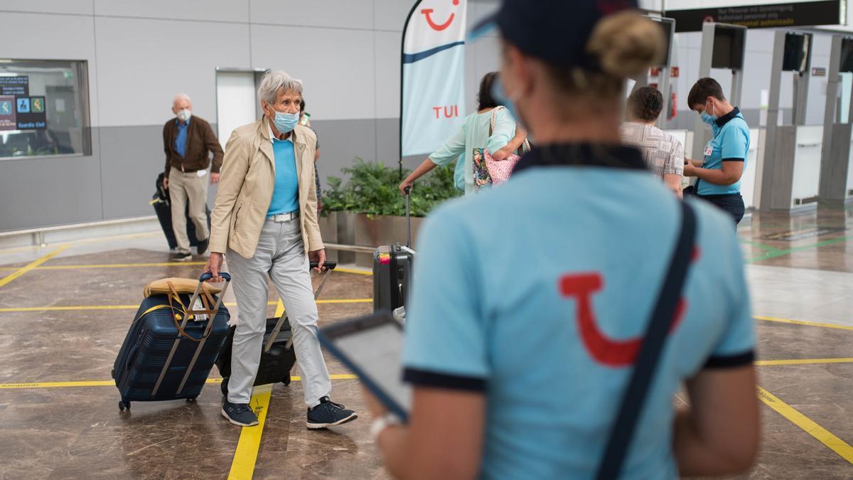 Una trabajadora de TUI espera a los turistas en el Aeropuerto de Tenerife Sur
