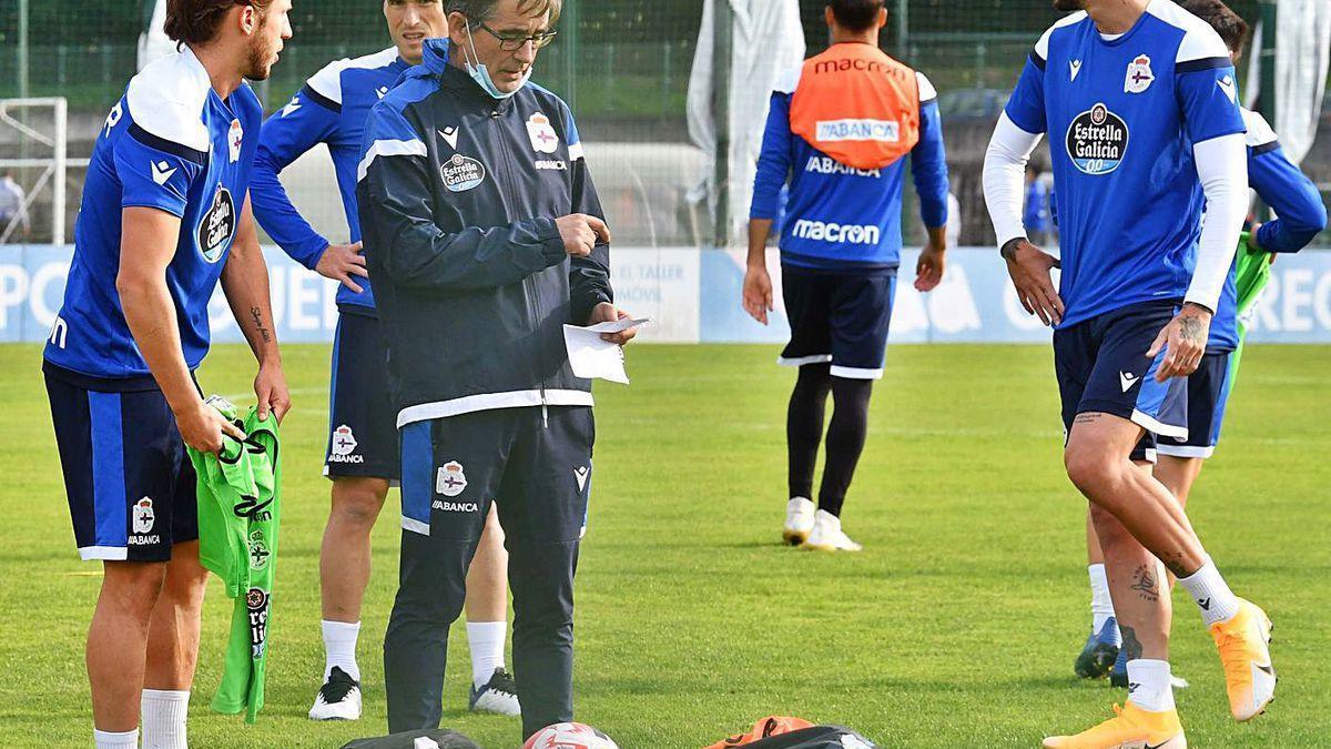 Fernando Vázquez, en el centro, revisa sus notas durante un entrenamiento.