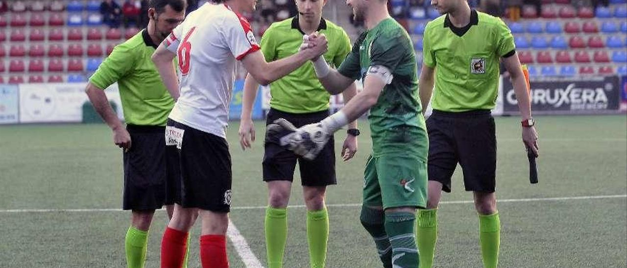 Adrián Torre saluda a Atienza, capitán del Vitoria, antes del inicio del partido.