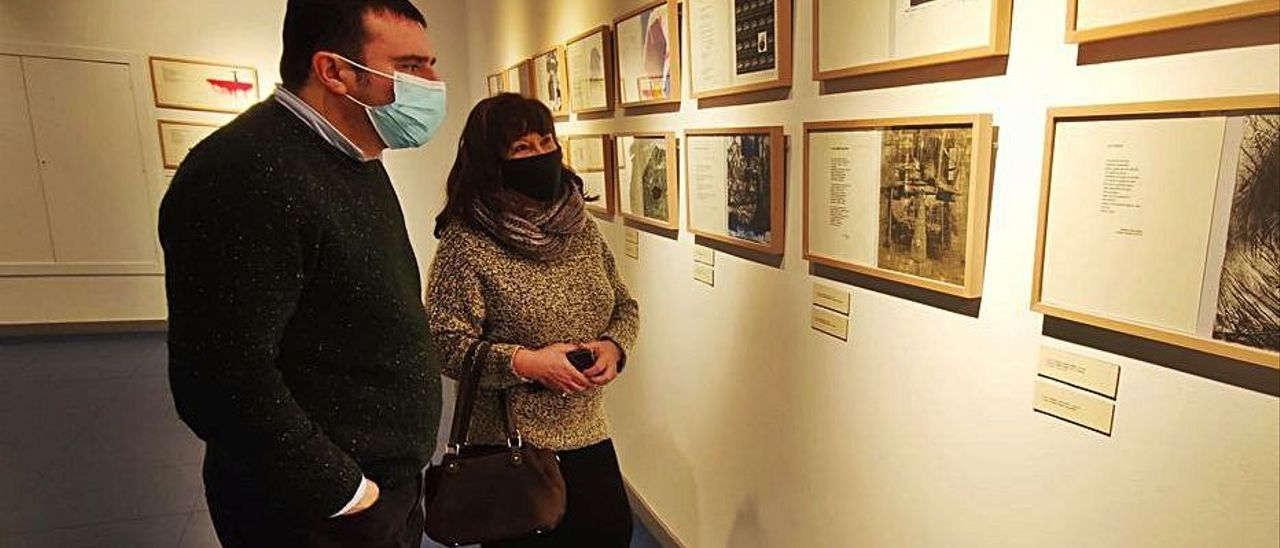"""Fermín Santos, promotor y editor de """"Al horru"""", y la escritora María Esther García contemplan algunas de las obras de la muestra."""