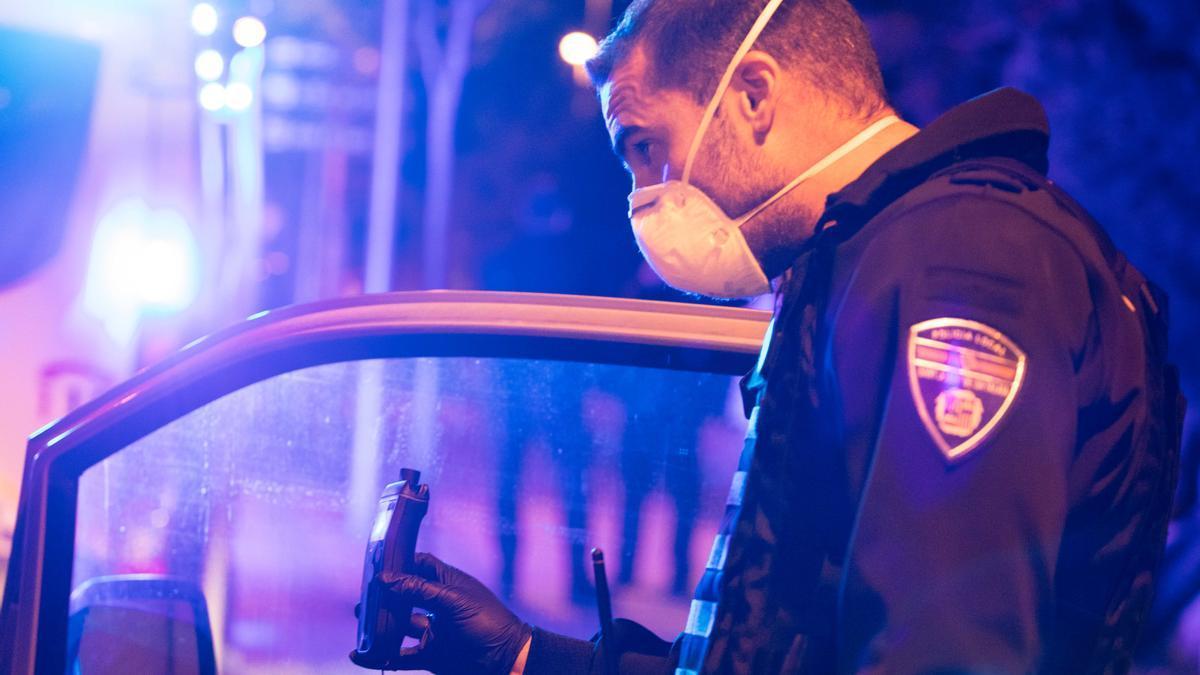 un policía sujeta un test de alcoholemia durante un control policial, en una imagen de archivo.