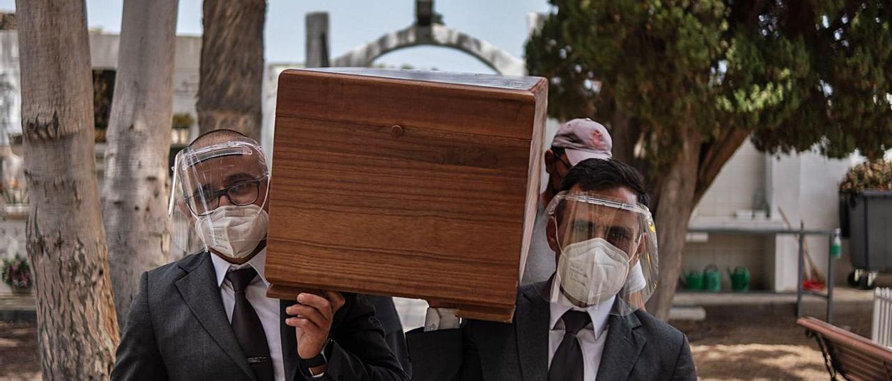 Operarios de la funeraria y del cementerio portan los ataúdes con los cadáveres de los migrantes.     ANDRÉS GUTIÉRREZ