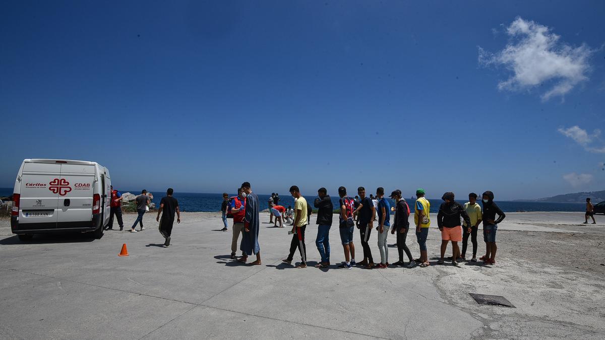 Un grupo de migrantes hace cola en Ceuta para recibir alimentos de Cáritas