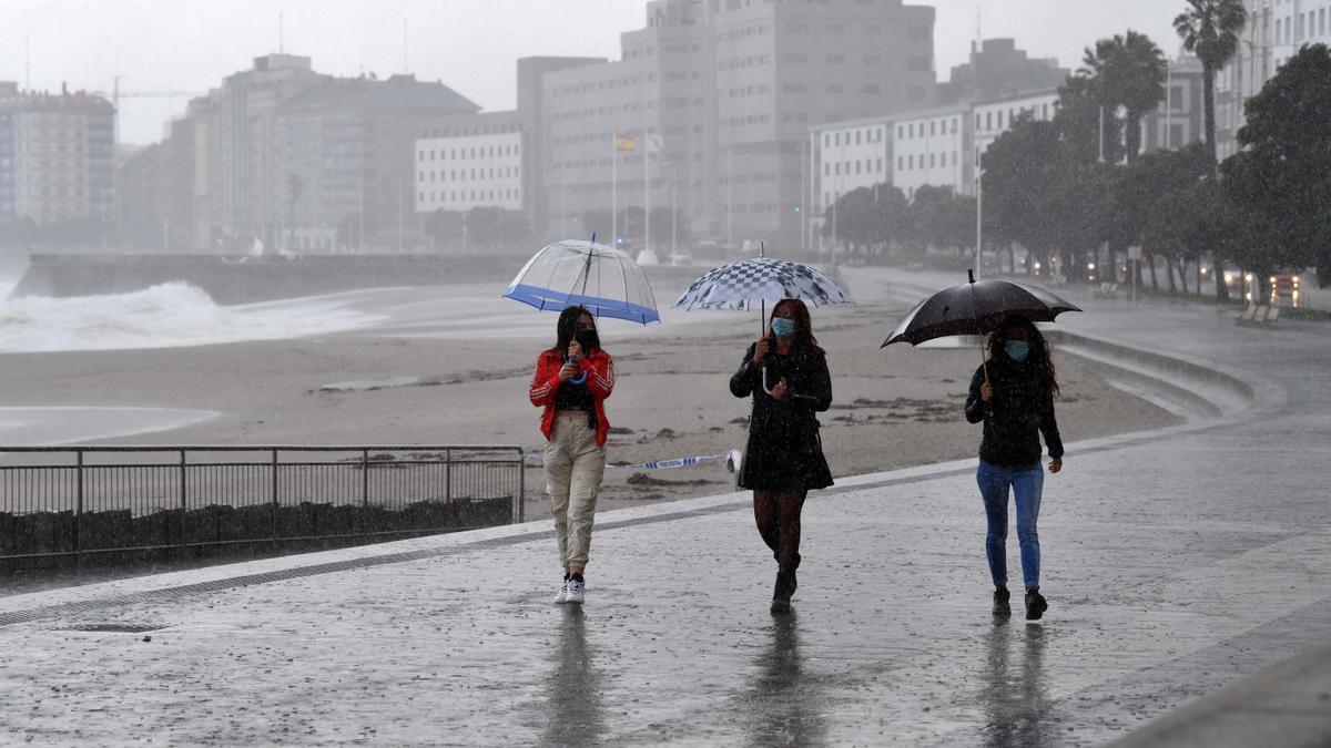 Viandantes en el paseo marítimo de Riazor durante el paso de una borrasca.