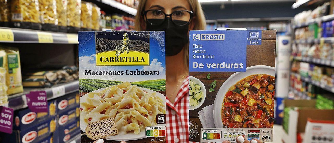 Una empleada de un Eroski muestra dos productos con diferente nota.