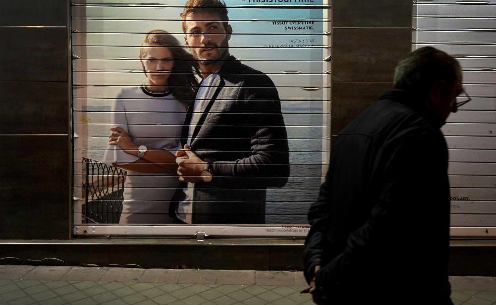 MADRID. 17.03.2020. CORONAVIRUS. Un hombre camina por la acera junto a un comercio cerrado.  FOTO: JOSE LUIS ROCA