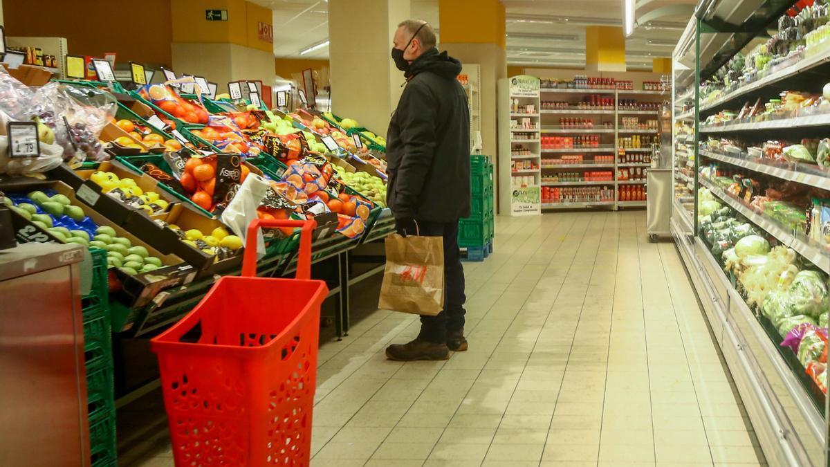 Imagen de archivo de un hombre en la sección de frutería de un supermercado.