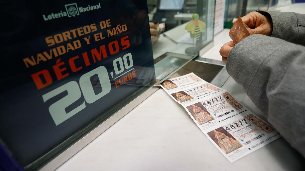 Una personas compra varios décimos de la Lotería.