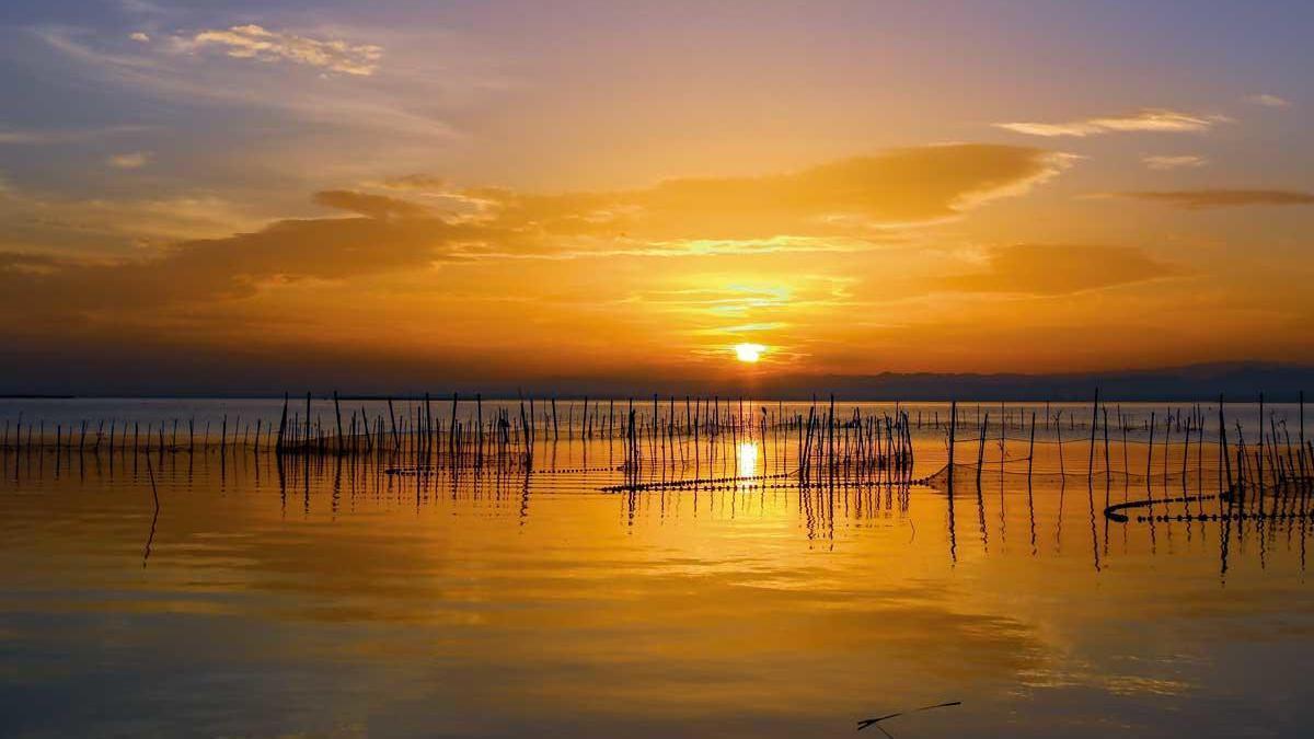 La puesta de sol va pintando la Albufera de Valencia de tonos rojizos y anaranjados.