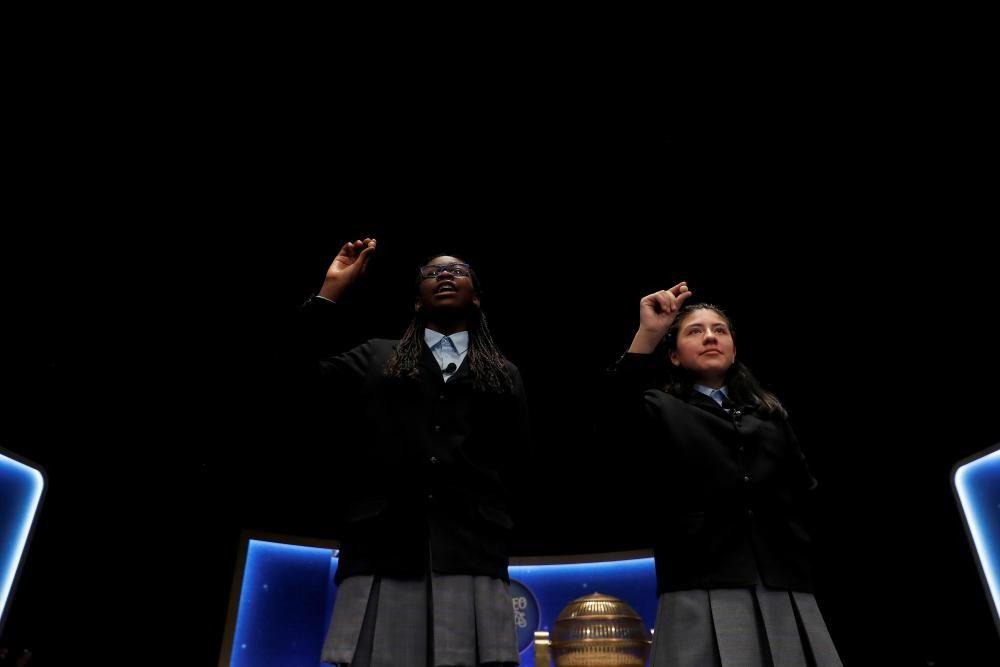 Las niñas del colegio de San ildefonso Yanisse Alexandra Soto (d) y Elisabeth Obarisiagbon Iyamu muestran las bolas con el número 69.823 que ha sido agraciado con uno de los quintos premios.