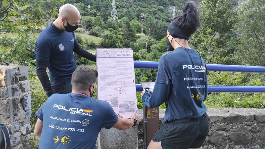 Agentes de la policía entregan uno de los carteles divulgativos en el Camino de Santiago
