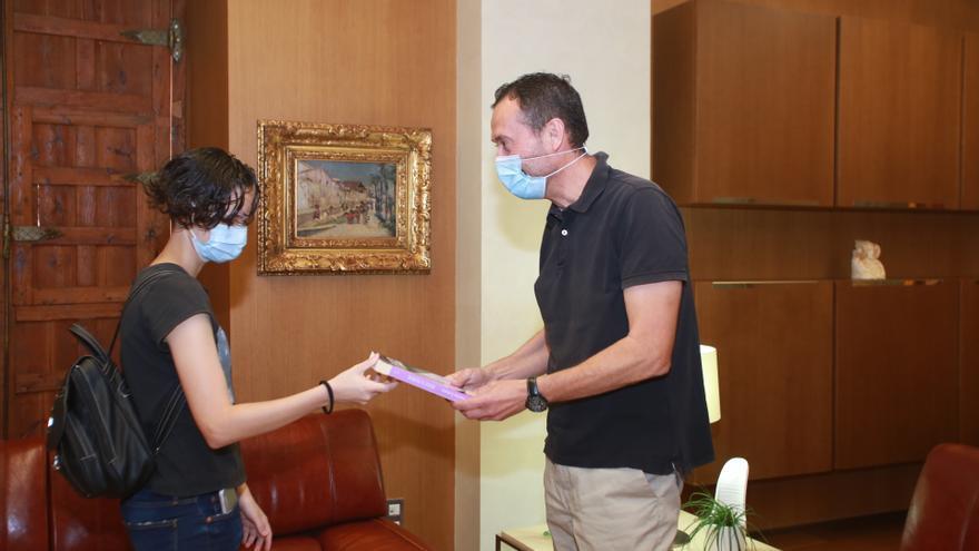 Patricia Aguilar le muestra al alcalde el libro en el que relata el infierno que pasó en Perú