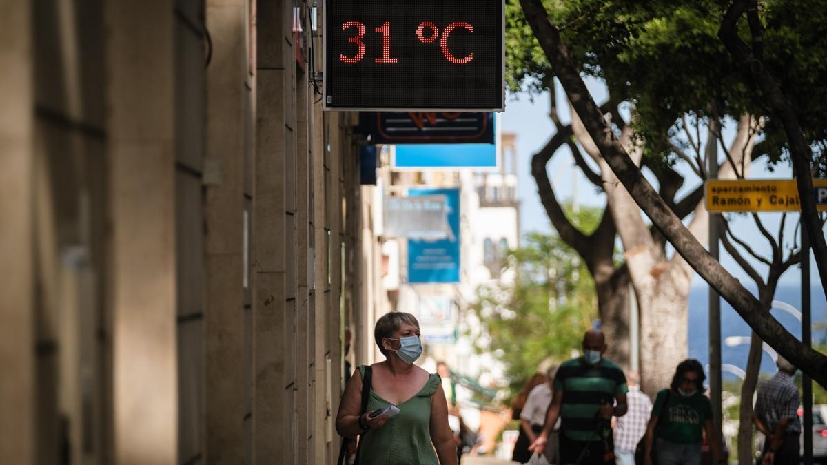 Una mujer con mascarilla camina por Santa Cruz de Tenerife durante una jornada de calor.
