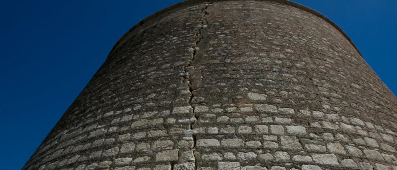 Una pareja ante el torreón del Castillo de San Fernando, que presenta una grieta de arriba abajo.