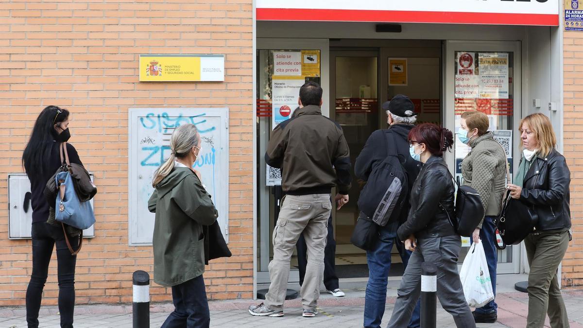 Varias personas en la puerta de una oficina del SEPE.