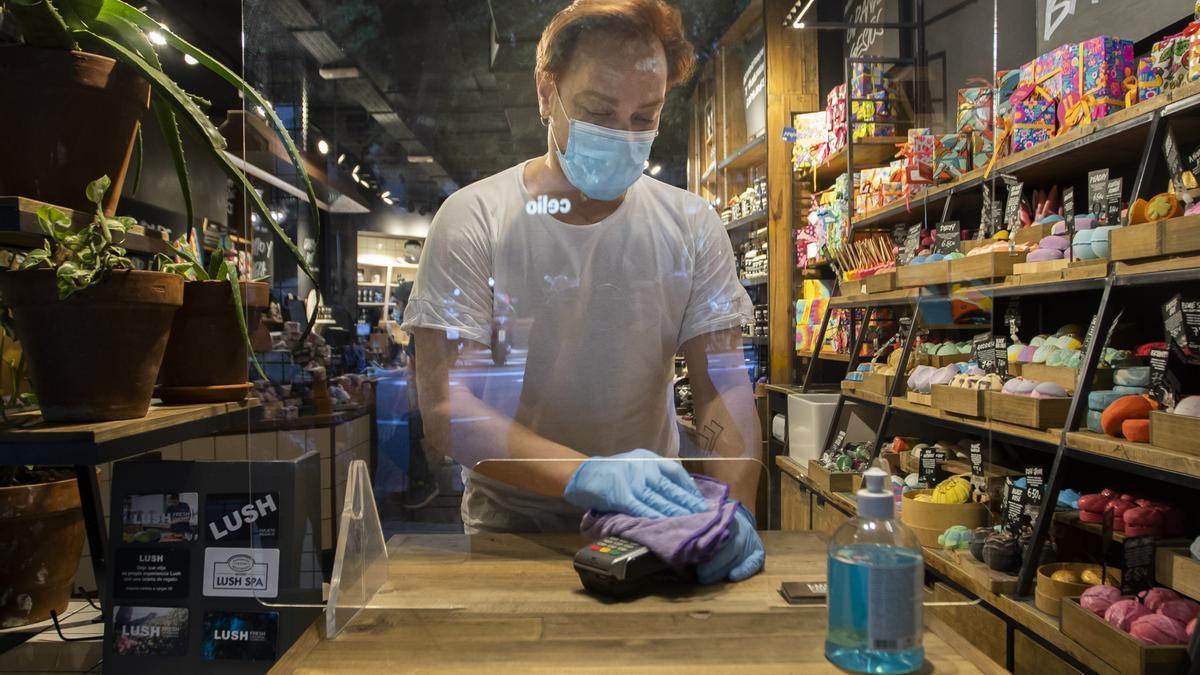 Un trabajador de un comercio de València durante la pandemia.