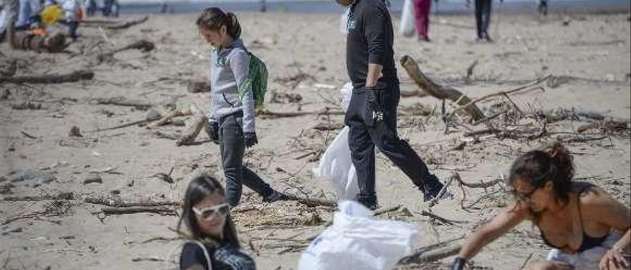 Asistentes, limpiando el arenal.