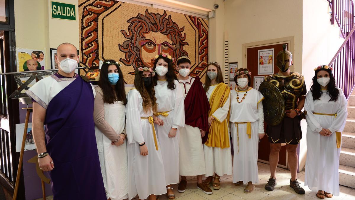 Profesores y alumnos vestidos de la época romana, ante el mosaico de Medusa.