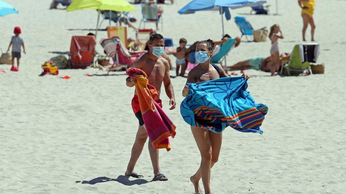 Dos bañistas con mascarilla en la playa, durante el pasado verano