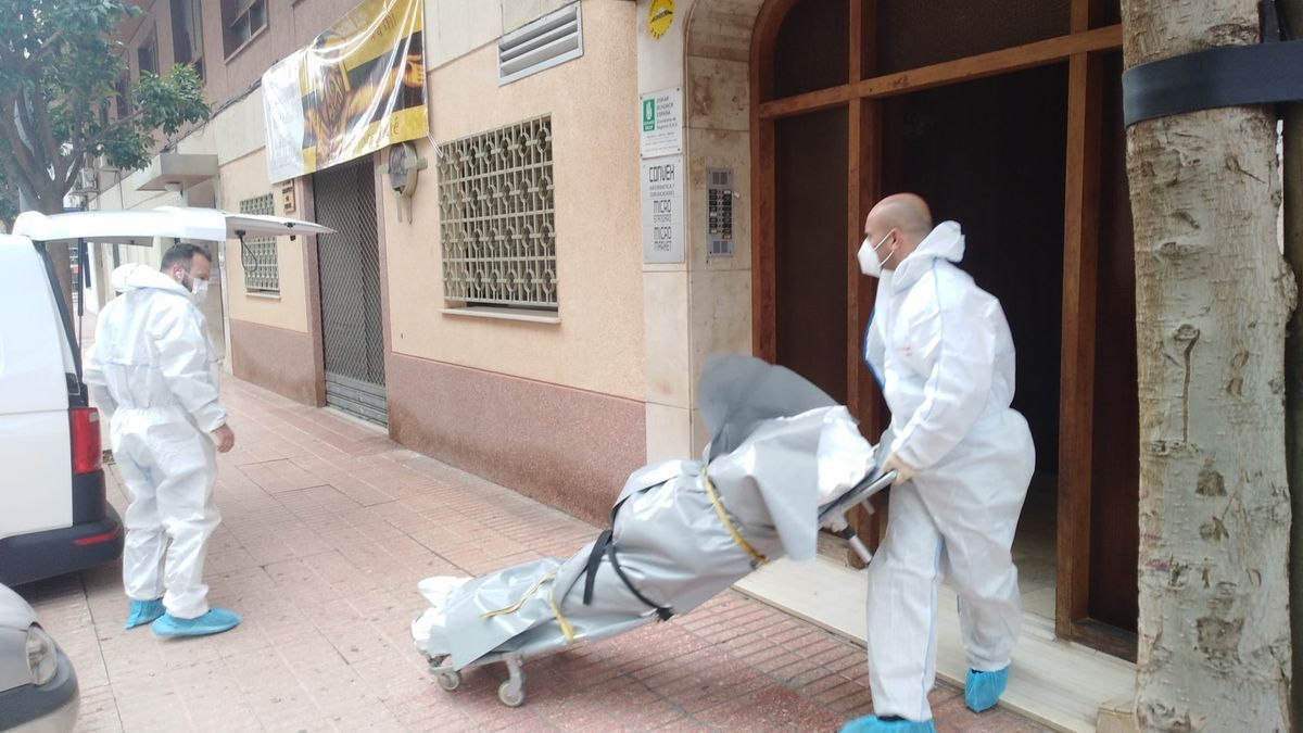 Operarios retiran el cadáver del hombre fallecido del lugar del crimen: su propia vivienda.